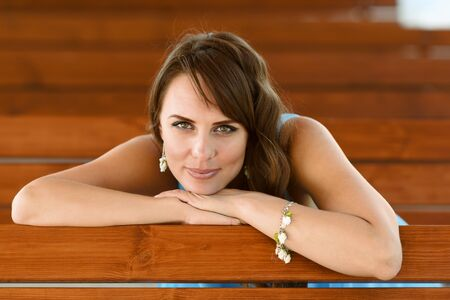 eyes hazel: Young smiling woman resting chin on palm, leaning on bench.
