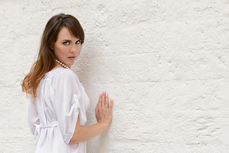 Young attractive woman leaning on plastered white wall and looking at camera Stock Photo
