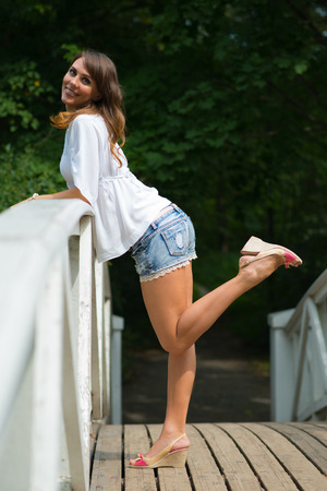 balustrade: Young woman leaning on balustrade and looking at camera, leg lifted and bent.