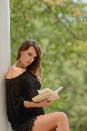attractive young woman leaning on column and reading book