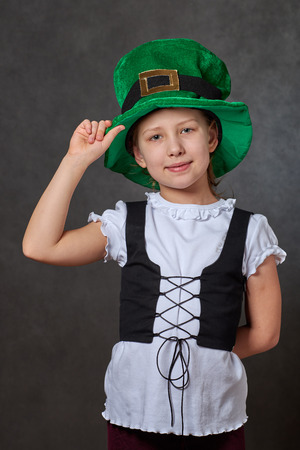 Young girl touching green leprechaun hat, wearing white blouse and black laced vest looking at camera Stock Photo
