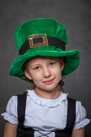 Young girl in green leprechaun hat, white blouse and black laced vest looking at camera