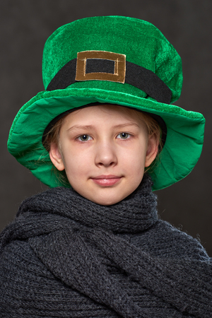 Young girl in green leprechaun hat and grey knitted scarf