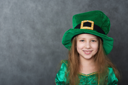 Girl in emerald dress and leprechaun hat looking at camera