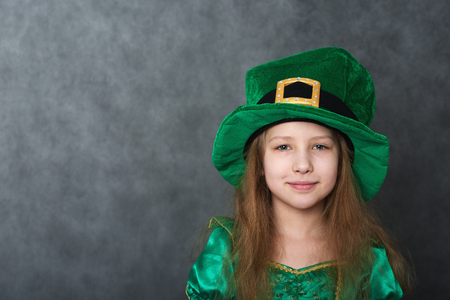 Girl in emerald dress and leprechaun hat looking at camera Stock Photo - 96814459