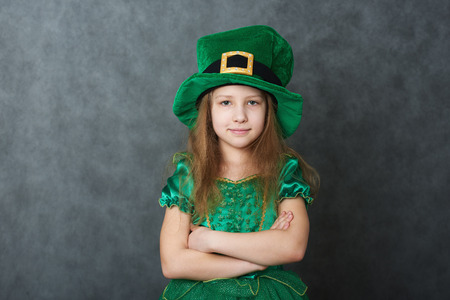Girl in emerald dress and leprechaun hat looking at camera, arms folded across her chest Stock Photo