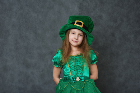 Girl in emerald dress and leprechaun hat looking at camera, arms behind her back