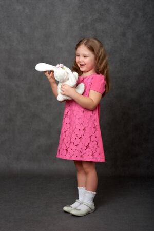 Girl in pink dress holding stuffed toy Stock Photo