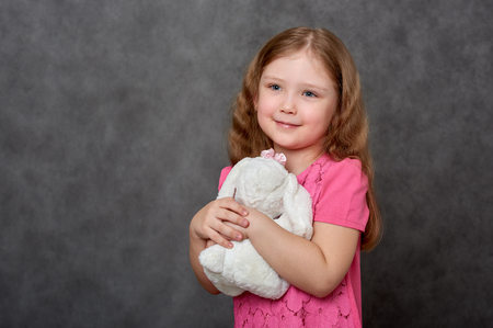 Girl in pink dress hugging stuffed toy Stock Photo