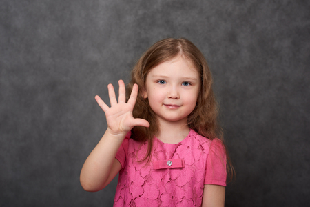 Girl in pink dress showing five fingers Stock Photo
