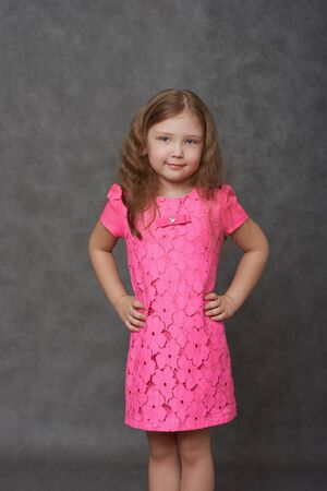 Girl in pink dress, arms on hips