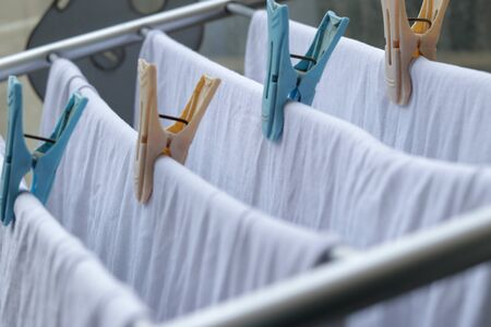 White clothes drying on standing clotheshores with clothespins white inner wear on Rack dryer Collapsible clothes horse with clothes plastic clothespins Stock fotó