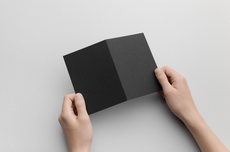 a6: Black A6 Bi-Fold  Half-Fold Brochure Mock-Up - Male hands holding a black bi-fold on a gray background.