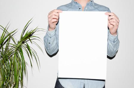 A3 ポスター モックアップ-白い背景の上にポスターを持ってデニム シャツの男。流行に敏感な美学 写真素材