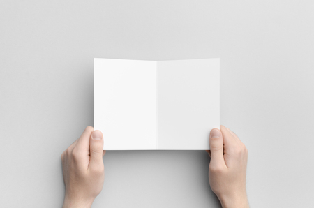 a6: A6 Bi-Fold  Half-Fold Brochure Mock-Up - Male hands holding a blank bi-fold on a gray background.