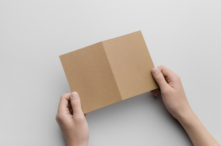 a6: Kraft A6 Bi-Fold  Half-Fold Brochure Mock-Up - Male hands holding a kraft bi-fold on a gray background.