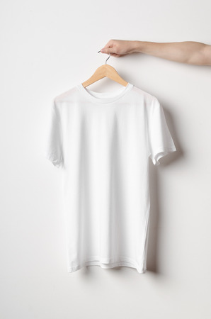 Men's Crew Neck T-Shirt Mock-Up - Man holding a white t-shirt on a wooden clothes hanger Banco de Imagens - 66784644