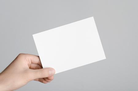 A6 Flyer  briefkaart  uitnodigingsmodel - Mannelijke handen die een lege vlieger op een grijze achtergrond houden. Stockfoto