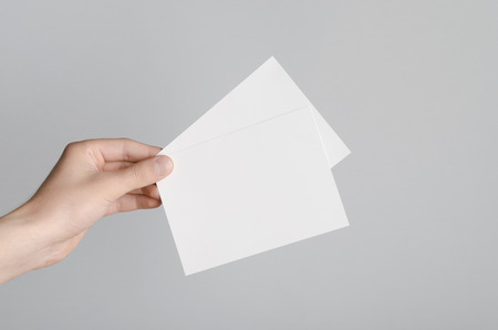 a6: A6 Flyer  Postcard  Invitation Mock-Up - Male hands holding blank flyers on a gray background.