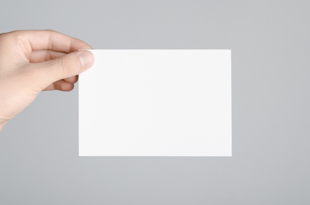 a6: A6 Flyer  Postcard  Invitation Mock-Up - Male hands holding a blank flyer on a gray background.