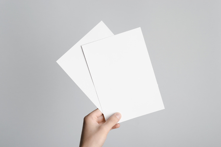 A5 Flyer / Invitation Mock-Up - Male hands holding blank flyers on a gray background. 免版税图像