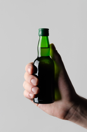 rakia: Miniature Spirits  Liquor Bottle Mock-Up - Male hands holding a liquor bottle on a gray background