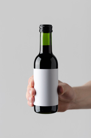 Wine Quarter  Mini Bottle Mock-Up. Blank Label - Male hands holding a wine bottle on a gray background