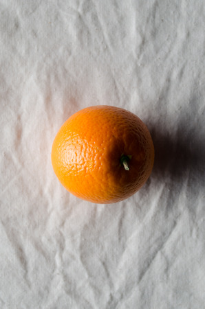 Orange on a white linen tablecloth. Banco de Imagens