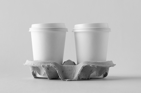 Two 12 oz. white coffee paper cups with lid in a holder. Blank Mock-Up. Banco de Imagens