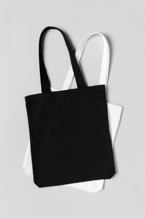 Black and white tote bags mockup on a grey background.