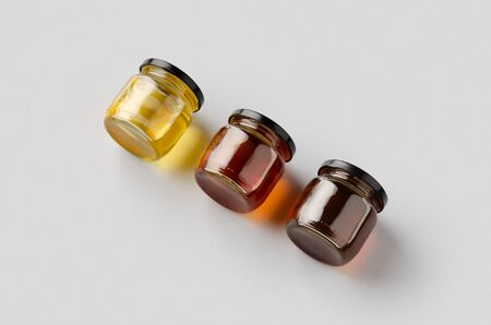 Honey jars mockup on a grey background. Three different colors.