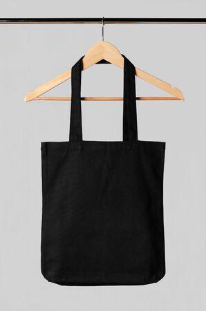 Black tote bag mockup hanging on a clothes hanger. Banco de Imagens