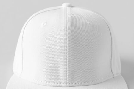White snapback cap mockup on a grey background, closeup.