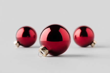 Three red glossy Christmas balls mockup on a seamless grey background. 免版税图像