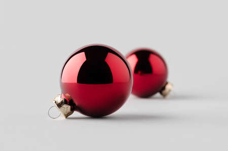 Two red glossy Christmas balls mockup on a seamless grey background.