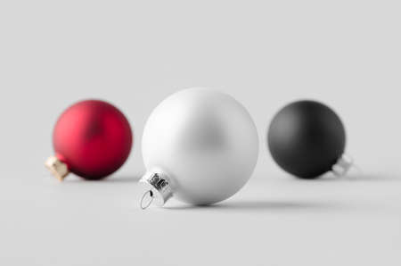 White, red and black matte Christmas balls mockup on a seamless grey background.