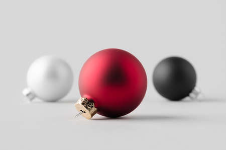 Red, white and black matte Christmas balls mockup on a seamless grey background. 免版税图像