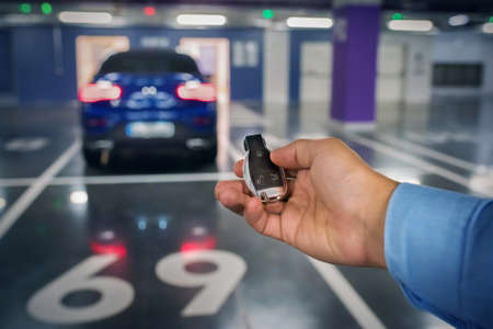 Car keys in a hand of the person against the background of the car. underground parking.