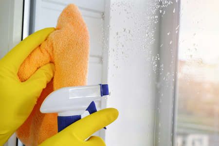 Washing windows with detergent and a rag. House cleaning. Household concept Imagens