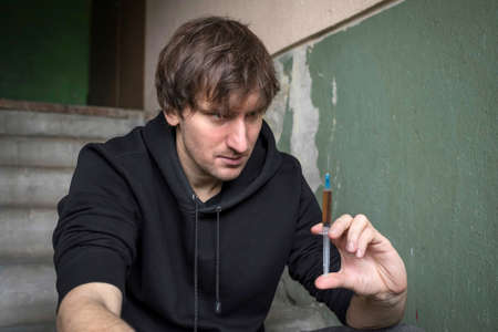 Man - addict with a syringe in his hand close-up. The fight against addiction. Addiction concept.