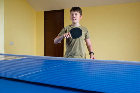 An 11-year old teenager with a tennis racket in his hands is playing table tennis. Sport lifestyle.