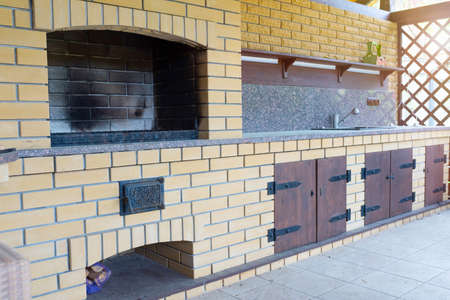 An outdoor fireplace for meals and barbeque made of bricks in the backyard.