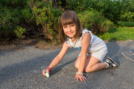 A little girl sits on the pavement and draws with crayons. Children's games in the open air. Archivio Fotografico
