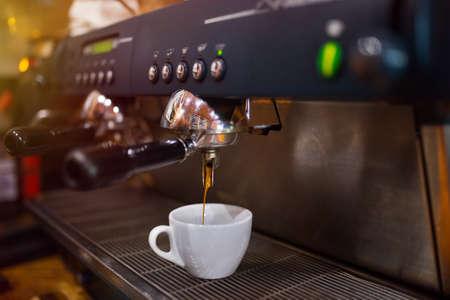 Close-up of espresso pouring from coffee machine. Prepares espresso