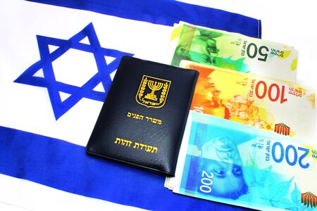 Passport Israel on the Israeli shekel (currency ILS) and IsraelI flag. (passport booklet, translate from the Hebrew and Arabic: Ministry of Interior, ID). Themes: economy, business, citizenship Reklamní fotografie