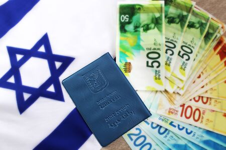 Israeli passport Teudat Zehut on the flag of Israel and Israeli shekel (currency ILS). Photo Themes: Israeli citizenship, Israeli citizen, economy in Israel, business in Israel, currency exchange Reklamní fotografie