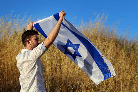 Israel, Israeli patriot, almost silhouette, with the flag of Israel over his head stands on the shores of the Mediterranean Sea at sunset. Independence day Israel, patriotic holiday concept