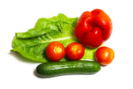 Vegetables on a white isolated background: green cucumber, red tomatoes, red bell pepper or sweet pepper and lettuce. Concept: Fresh vegetables gifts of nature