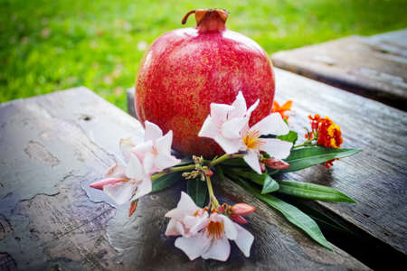 Still life: a branch with light purple flowers and a red juicy large pomegranate on vintage wooden planks. Concept gifts of nature