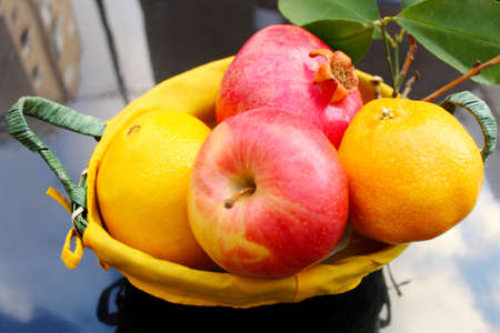 Various fresh fruits in basket on the on a black reflective surface: apple, pomegranate, orange. Concept gifts of nature Banque d'images
